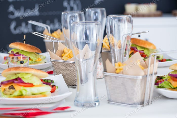 Hamburgers and glasses on table