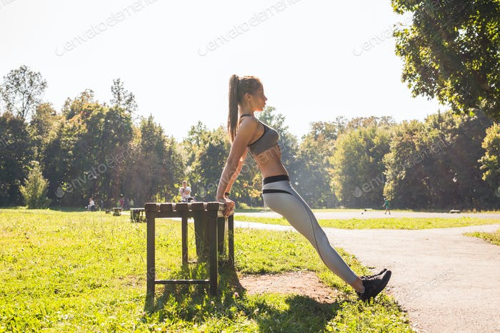 Young fit woman exercising by doing push-ups outdoors