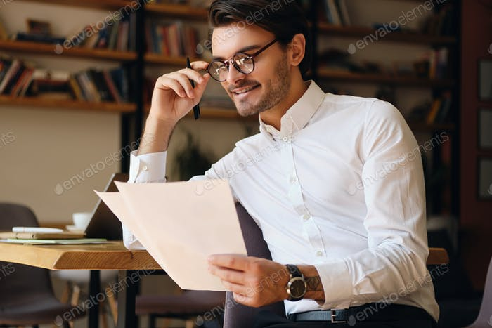 Young smiling businessman in eyeglasses and white shirt happily working with papers in modern office
