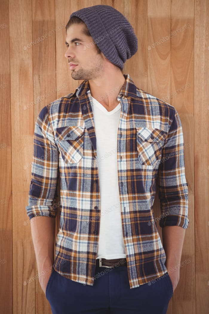 Confident hipster looking away while standing against wooden wall