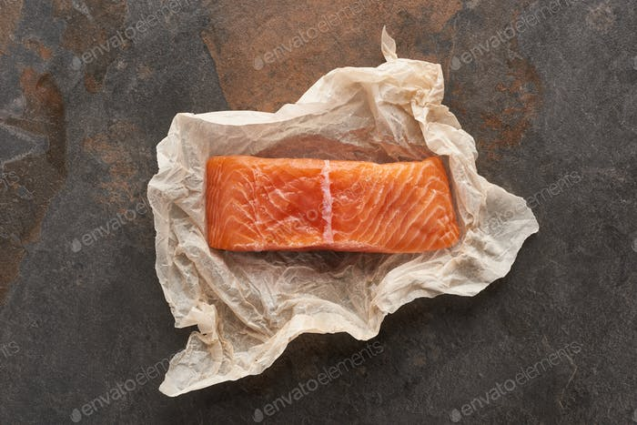 Top View of Uncooked Salmon Steak on Bakery Paper on Stone Table