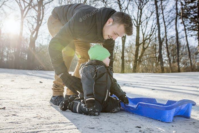 Junger Vater Vorbereitung Baby Junge auf Rodeln