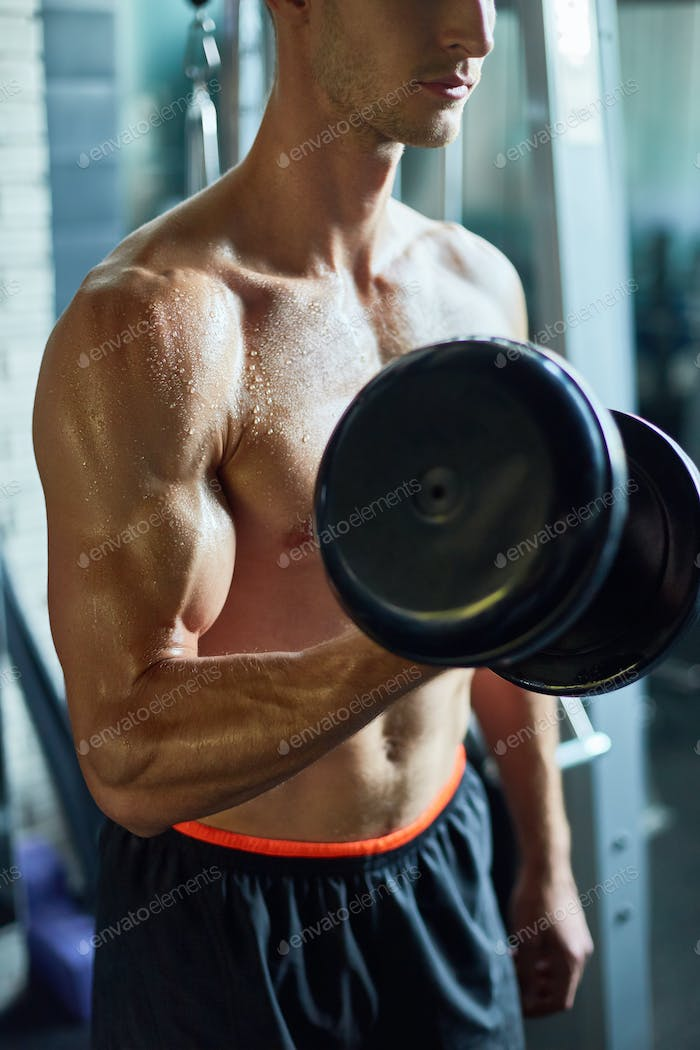 Muscular Sportsman Working Out in Gym