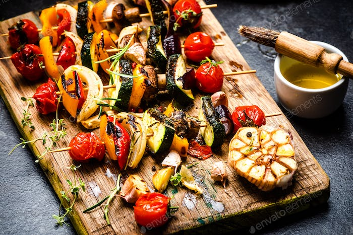 Serving Grilled BBQ Vegetables Skewers with Fresh Herbs, Marinate and Spices on Wooden Board