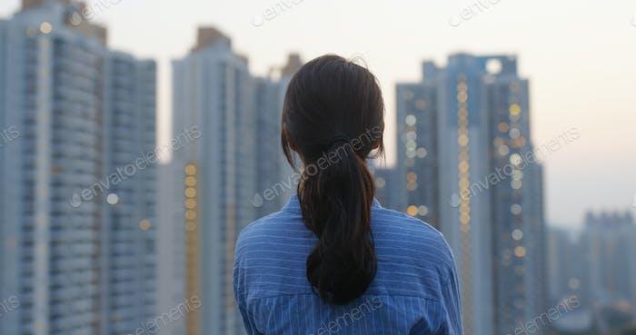 Женщина смотрит на город вечером