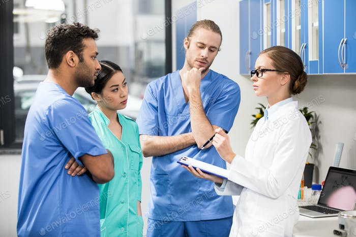group of medical workers discussing work in laboratory