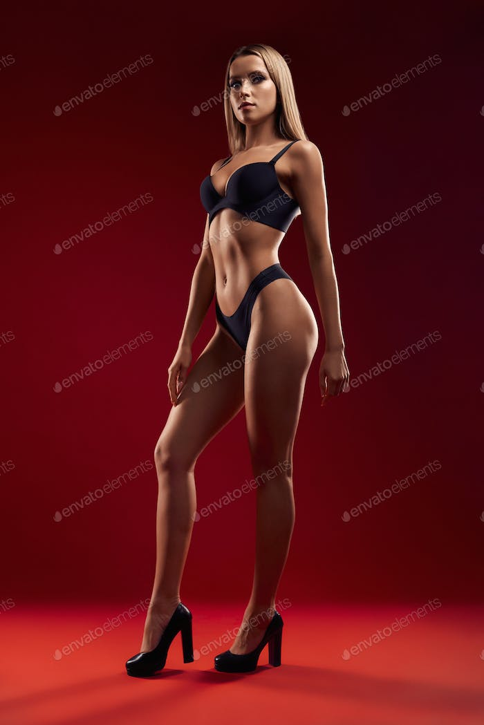Sexy woman in lingerie isolated on red