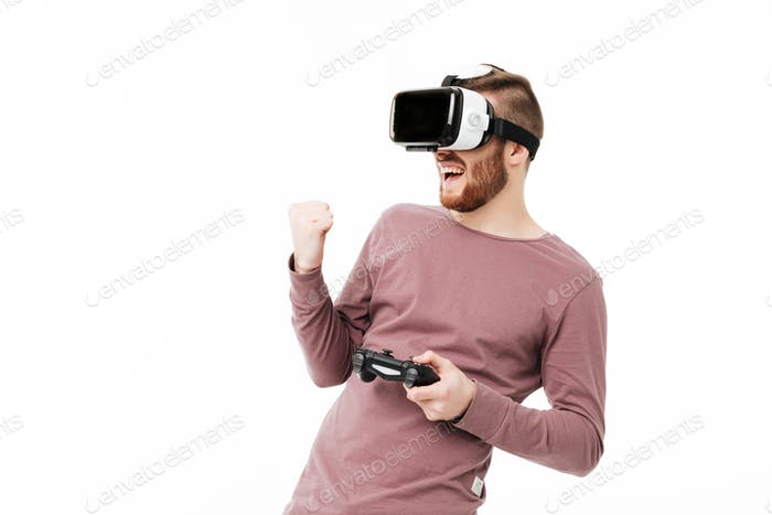 Young man standing in virtual reality glasses with joystick in hand and showing yes gesture