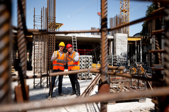 Architect and structural engineer in orange work vests and helmets discuss a building project on the