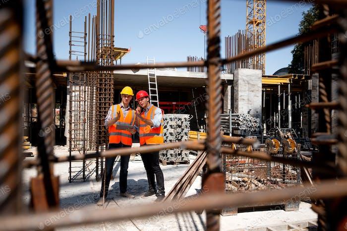 Architekt und Bauingenieur in orangefarbenen Arbeitswesten und Helmen diskutieren ein Bauprojekt auf der