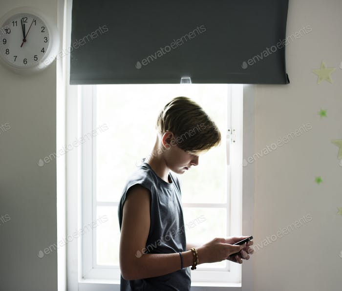 Young caucasian boy using mobile phone in bedroom