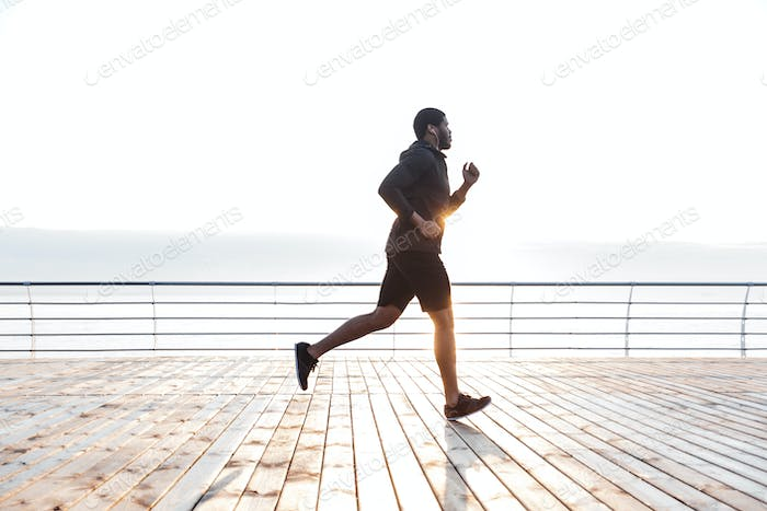 Handsome african american young sportsman running on pier