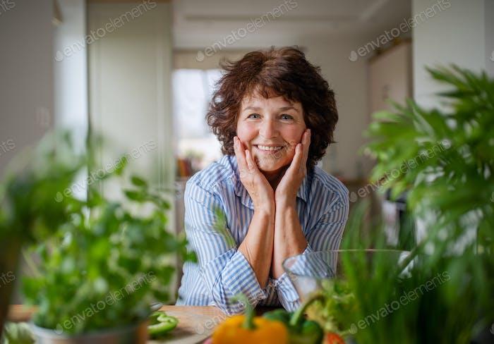 Senior woman in kitchen at home, looking at camera