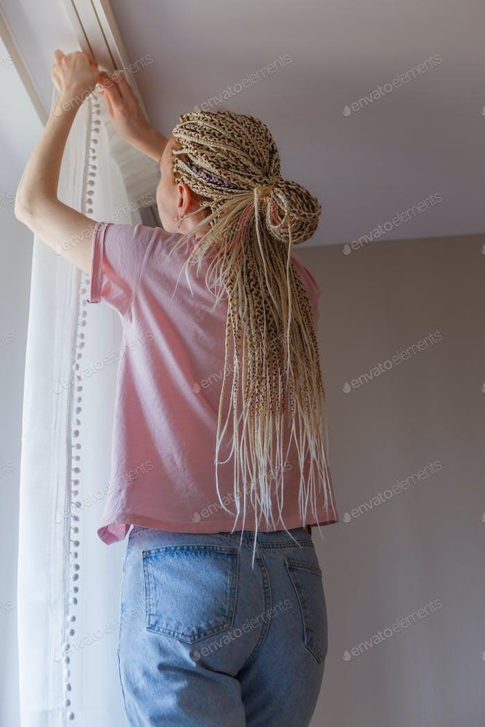 Frau hängen Vorhänge am Fenster