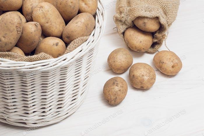 Kartoffeln im Korb auf weißem Holzhintergrund