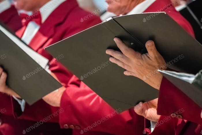Mens choir members holding singing book