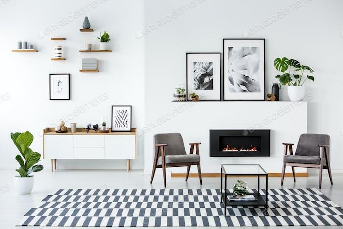 Fireplace between grey armchairs in modern living room interior
