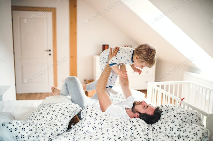 Father with a toddler boy having fun in bedroom at home at bedtime.