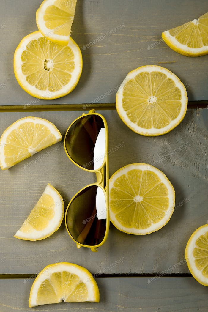 Yellow aviator sunglasses near lemon on grey wooden board. sunglasses on wooden background,