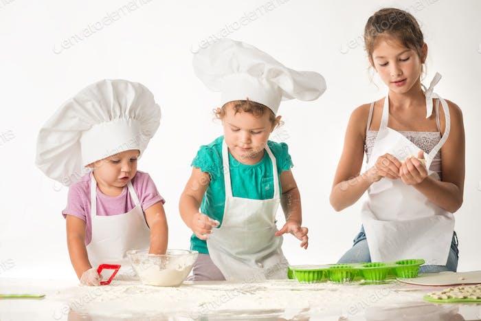 Cute little children in a cook suit cook cookies