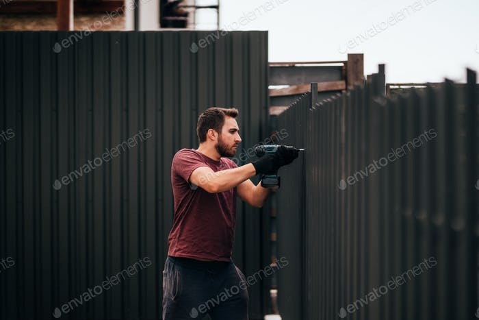 Industrial construction handyman using screwdriver for installing fence