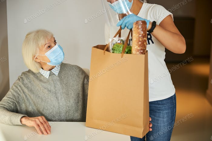 Pensioner looking at a volunteer with a paper bag