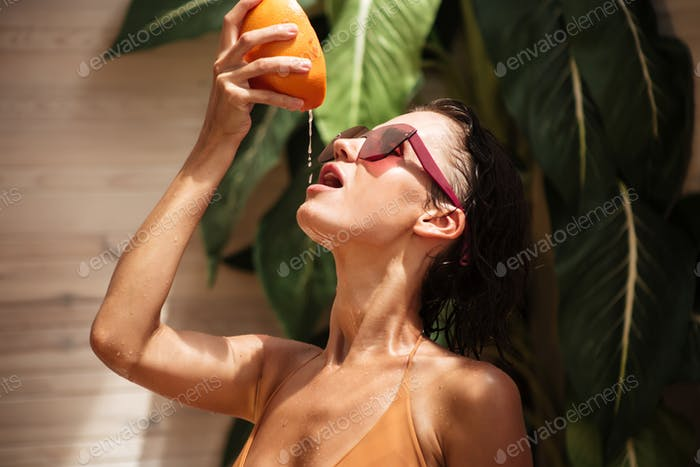Portrait of pensive girl in beige bikini and sunglasses standing and squeezing grapefruit juice