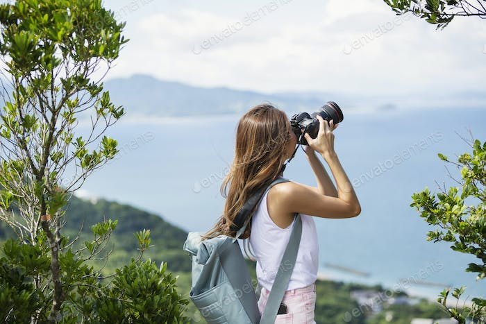 Japanese woman carrying backpack taking photograph on a cliff, ocean in the background.