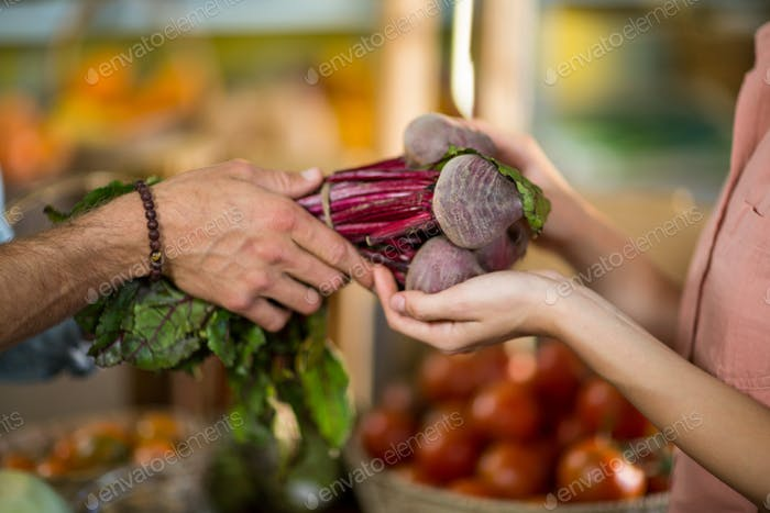 Vendor giving beetroot to the woman at the grocery store
