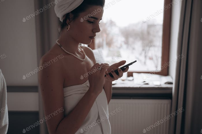 beauty woman in a bathrobe and with a towel on her head using smartphone