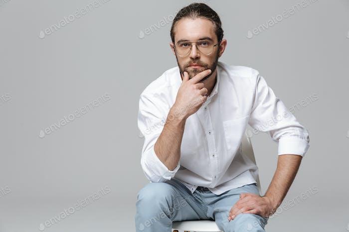 Hombre barbudo guapo posando aislado sobre fondo gris de pared.