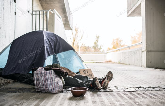 Legs and feet of homeless beggar man lying on the ground in city, sleeping in tent.