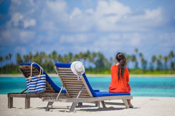 Back view of young woman relaxing at beach chairs