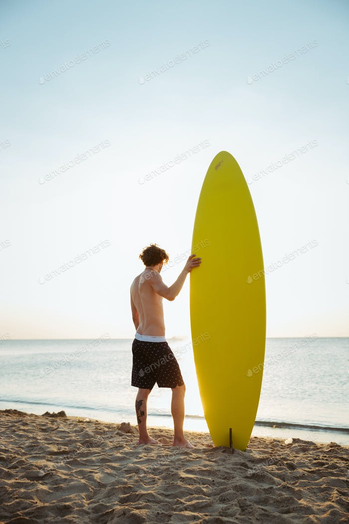 Man with his surfboard standing on the beach