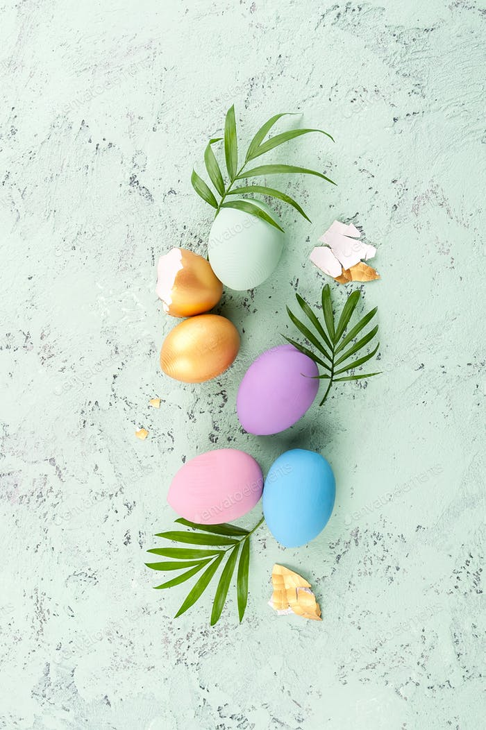 Colored Easter eggs and green leaves on a light blue aged backgr