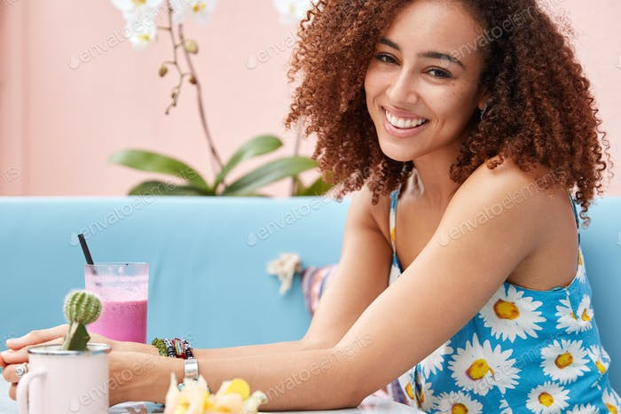 Sideways shot of young attractive young smiling woman with Afro hairstyle, dressed in bright summer