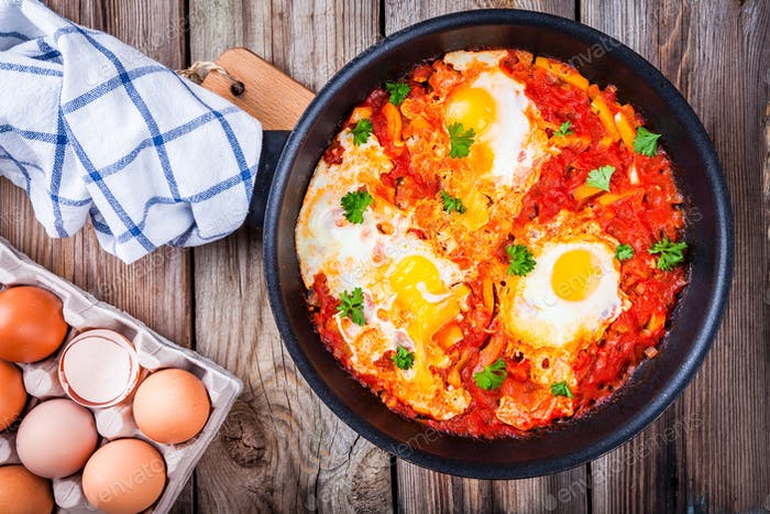 Shakshuka. Fried eggs with tomato, paprika and parsley