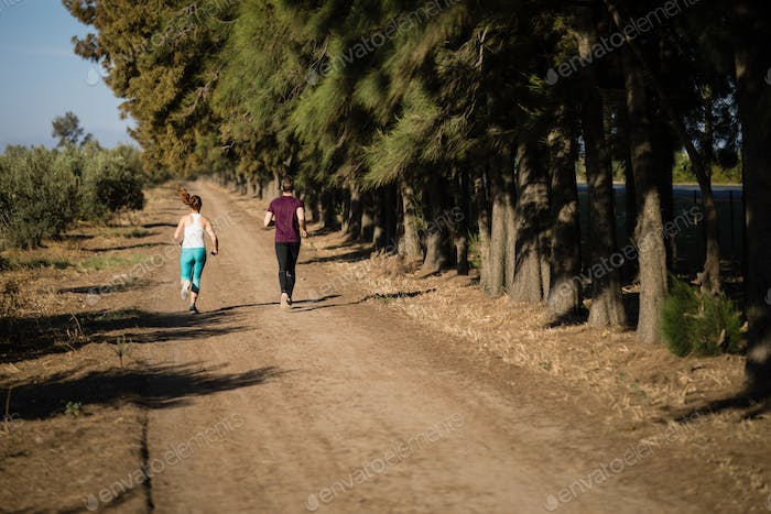 Rear view of young couple running on dirt road