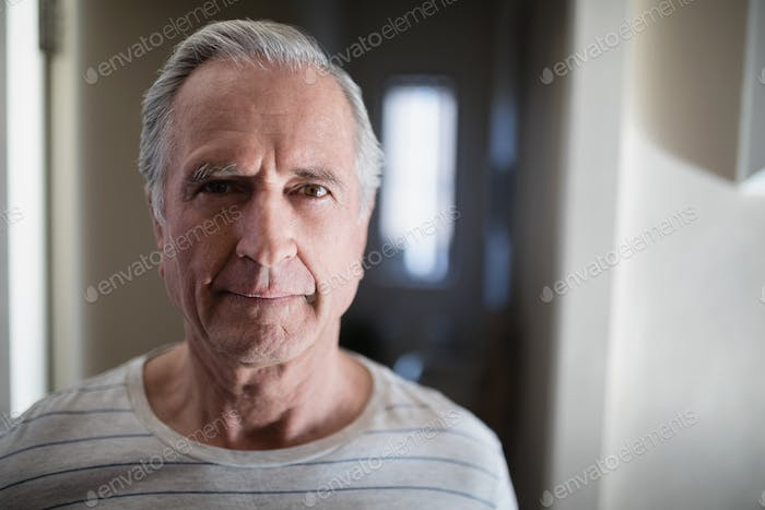 Close-up portrait of senior male patient standing in corridor