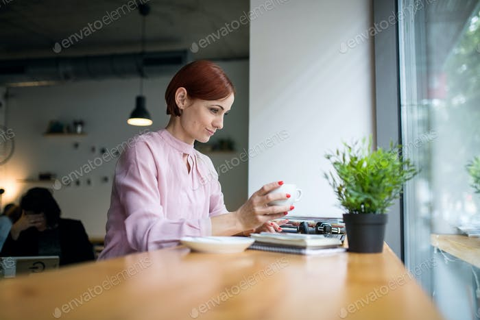 A portrait of woman with coffee sitting at the table in a cafe, working.