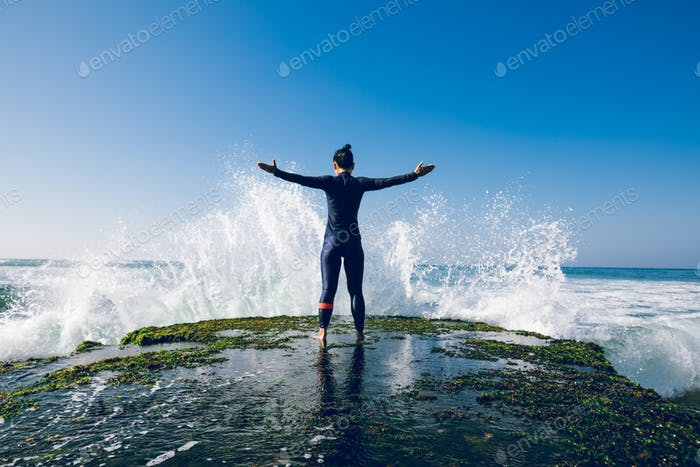 Strong woman open arms to the giant waves at seaside
