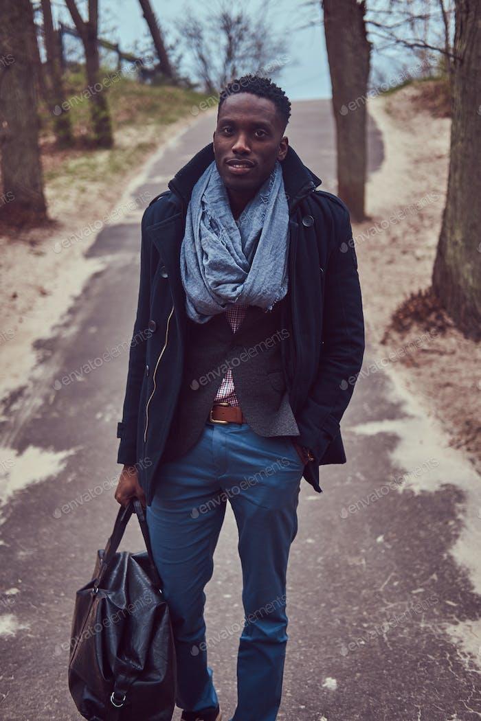 Stylischer afroamerikanischer Typ in Freizeitkleidung mit einer Tasche walki
