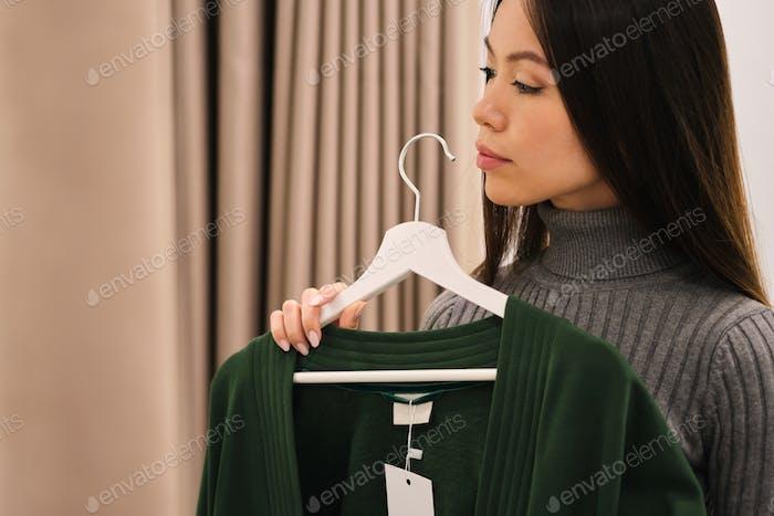 Side view of beautiful Asian girl thoughtfully choosing cardigan in fashion store