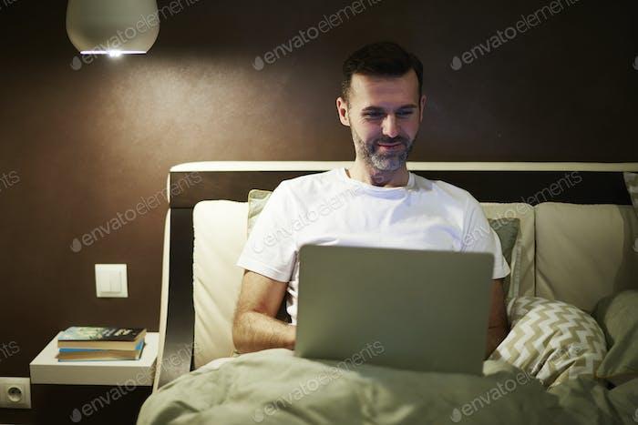 Mature man using a laptop at night