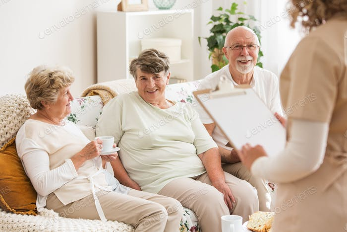 Happy elders sitting on a couch while talking to a nurse