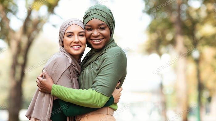 Zwei muslimische Damen In Hijab Umarmt Posing Stehen Im Park