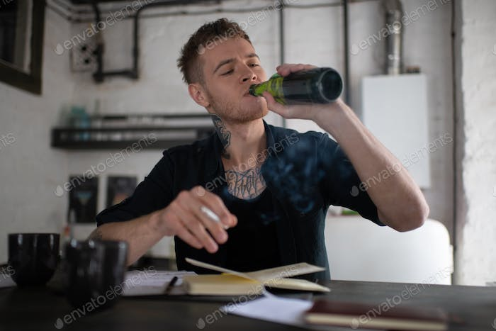 Man drinking beer and smoking cannabis while working by table