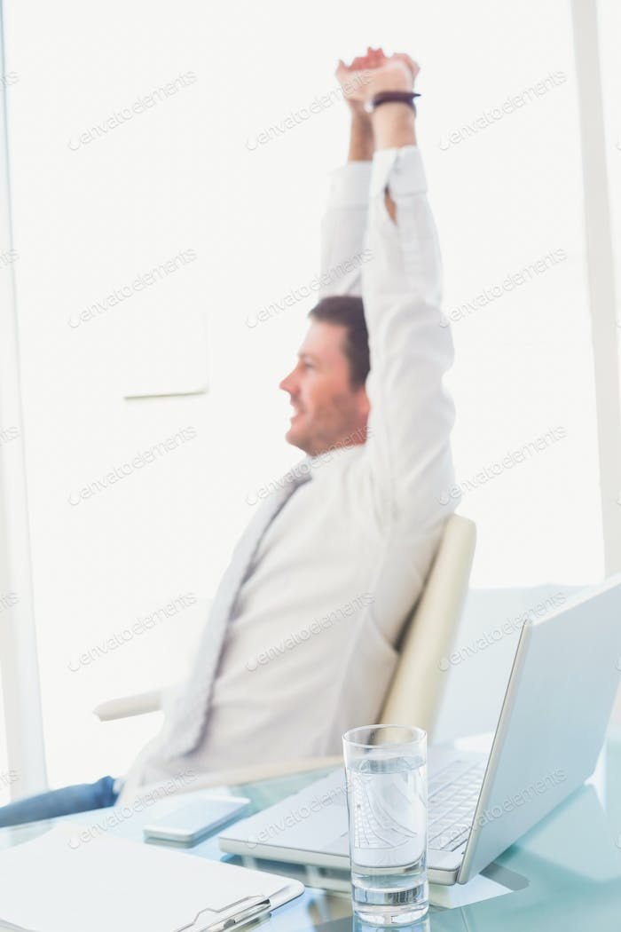 Smiling businessman stretching at desk in his office
