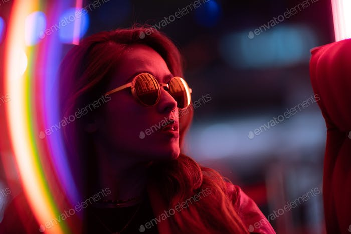 Portrait of young woman with long black hair and red leather jacket with neon pink lights