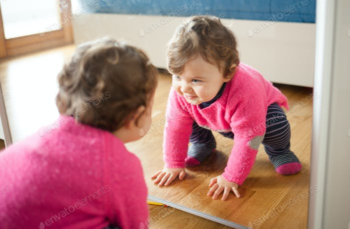 Toddler baby girl playing with mirror in the bedroom